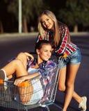 驾驶购物车的两个愉快的美丽的青少年的女孩户外 图库摄影