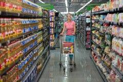驾驶购物车的妇女,当杂货在超级市场时 免版税图库摄影