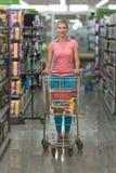 驾驶购物车的妇女,当杂货在超级市场时 图库摄影