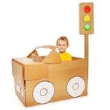 驾驶他的手工制造纸板汽车的小男孩 免版税图库摄影