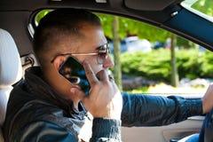 驾驶他的敞篷车汽车的年轻人 免版税图库摄影