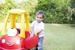 驾驶他的玩具的愉快的小男孩 库存图片