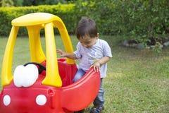 驾驶他的玩具的愉快的小男孩 免版税库存图片