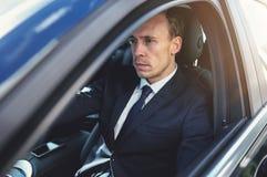 驾驶他的黑时髦的汽车的严肃的商人 免版税库存图片