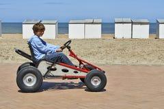 驾驶Quadricycle的年轻男孩 图库摄影