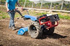 驾驶rototiller拖拉机单位的女工准备土壤 免版税库存照片