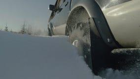 驾驶SUV汽车在森林公路的冬天有雪的 在森林困住的汽车 特写镜头 免版税库存图片
