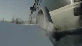 驾驶SUV汽车在森林公路的冬天有雪的 在森林困住的汽车 特写镜头 库存图片