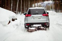 驾驶SUV汽车在森林雪路的冬天 库存图片