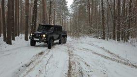 驾驶SUV 6x6由越野在冬天森林里,前面左看法 股票录像