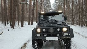 驾驶SUV 6x6由越野在冬天森林里,正面图 股票视频