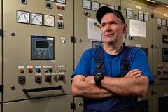 骄傲和愉快的技工/总工程师,摆在与在一只工业货船的机舱横渡的他的胳膊 免版税库存照片
