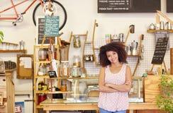 骄傲地站立在她的咖啡店的小企业主 库存图片