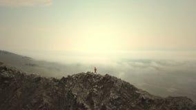 -骄傲地站立在寒冷的山上面,阴天的女性徒步旅行者的空中关闭在秋天 股票录像