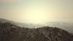 -骄傲地站立在寒冷的山上面,阴天的女性徒步旅行者的空中关闭在秋天 影视素材