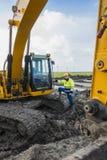 骄傲地站立在他的挖掘机旁边的建筑工人 图库摄影