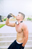 年轻骄傲的人在非常坚硬训练以后喝加强的水 库存图片