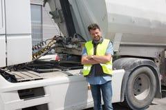 骄傲的司机或运输业者在卡车和拖车前面, 免版税库存图片