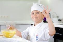 骄傲的小男孩烘烤在厨房里 免版税库存图片