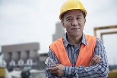 骄傲的工作者画象有胳膊的在防护工作服横渡了在工厂外面 免版税库存照片