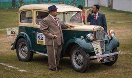 骄傲的所有者在他的奥斯汀七1938式样葡萄酒汽车旁边站立在政治家葡萄酒汽车集会 免版税库存图片