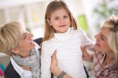 骄傲的抓住小女孩的祖母和母亲 图库摄影