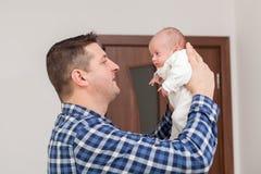 骄傲的父亲在手上的抱着他的新生儿 库存照片