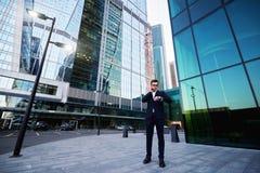 骄傲的男性金融家在手机交谈时检查时间 库存图片