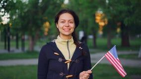骄傲的美国挥动美国旗子的公民微笑的妇女慢动作画象,看照相机和微笑 绿色结构树 股票视频