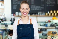 骄傲的年轻女性咖啡馆所有者 库存照片