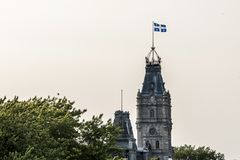 骄傲魁北克市加拿大蓝色白旗在魁北克的国民大会议会大厦顶部钟楼  免版税库存图片