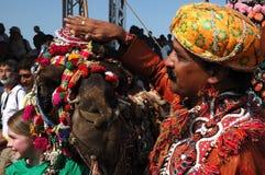 骆驼和他的在骆驼装饰竞争, Pushkar, Rajastan的责任人 免版税库存图片