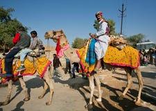 骆驼和徒步旅行队车手五颜六色的有蓬卡车在传统服装 免版税库存照片
