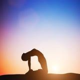骆驼瑜伽姿势的妇女思考在日落的 禅宗 免版税库存照片