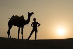 骆驼男孩横穿Silhoutte在塔尔沙漠 图库摄影