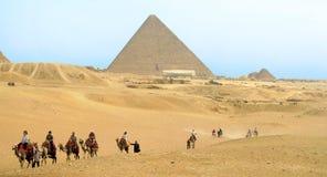 骆驼的游人在Cheops前面金字塔  免版税库存照片