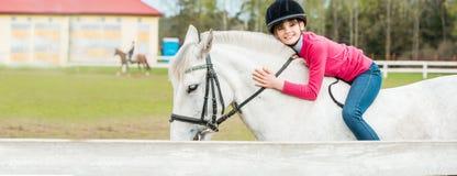 骑一个白马的一个甜女孩,运动员参与马术运动、女孩拥抱和亲吻马 免版税库存图片
