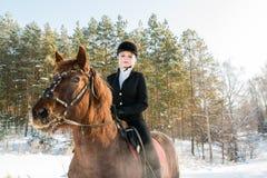 骑一匹马的年轻美丽的女孩骑师在冬天森林里 免版税库存图片