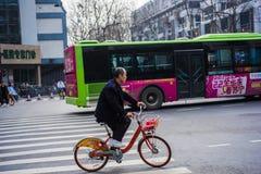 骑一辆公开自行车的一个人穿过了南京街道  图库摄影