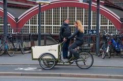骑一辆减速火箭的电自行车的妇女 免版税图库摄影