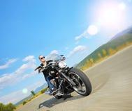 骑一辆定制的摩托车的骑自行车的人在一条开放路 免版税库存图片