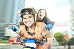 骑一辆摩托车的两名妇女在城市 库存照片