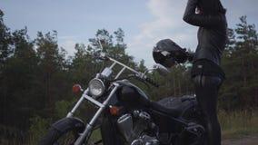 骑一辆经典摩托车的一件黑皮夹克和盔甲的技巧白种人妇女 女孩去除盔甲身分 股票录像