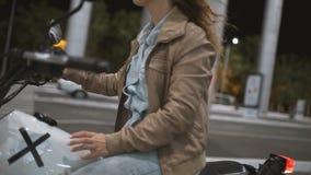 骑一辆老咖啡馆竟赛者摩托车的美丽的少妇在街道 夜路的女性骑自行车的人 股票录像