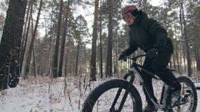 骑一辆肥胖自行车的专业极端运动员骑自行车的人在户外 在冬天雪森林人的骑自行车者乘驾 股票视频