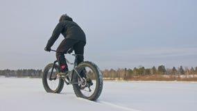 骑一辆肥胖自行车的专业极端运动员骑自行车的人在户外 骑自行车者乘驾在雪冰的冬天 人 股票录像