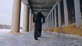 骑一辆肥胖自行车的专业极端运动员骑自行车的人在户外 骑自行车者乘驾在雪冰的冬天 人 股票视频