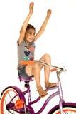 骑一辆自行车用她的手的逗人喜爱的女孩在天空中 免版税库存图片