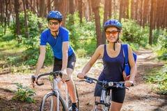 骑一辆自行车的夫妇在森林里 免版税库存图片