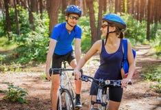 骑一辆自行车的夫妇在森林里 库存照片